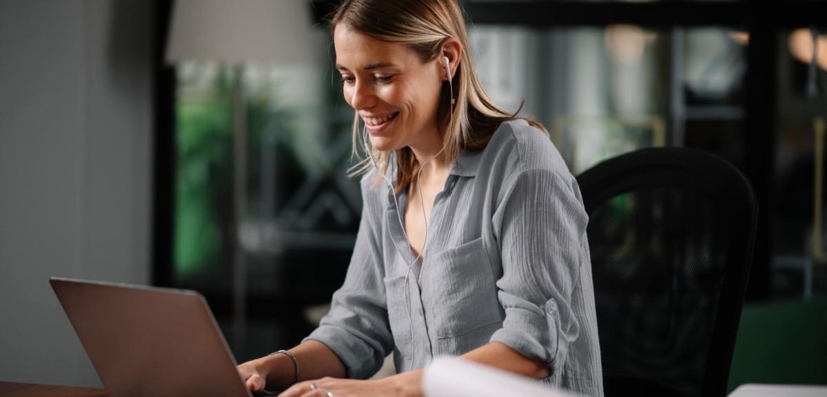 Dame på laptop med øreplugger delater på online kurs